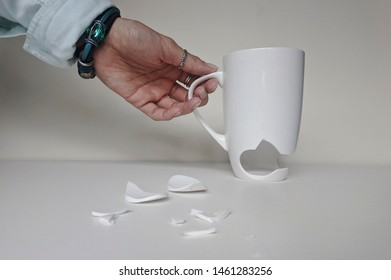 Woman's picking up broken White Cup with Few Little Pieces. Concept Disintegration. Broken Ceramic Mug