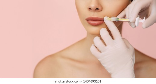 woman's plumper lips, getting bigger lips. prick of a syringe for the lips. injections for bigger volume of lips on pink