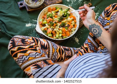 Woman's pregnant belly with hands and healthy food. Baked, roasted vegetables mix in skillet. Vegan lunch or vegetarian diet dinner for waiting, expecting baby women. Top above view.