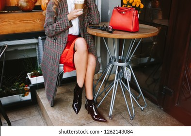 Woman's pretty legs, girl sitting in outdoor cafe, holding cup of cappuccino, coffee, late in hands. Wearing high heels, stylish jacket,red leather skirt and red handbag Outside cafe city background