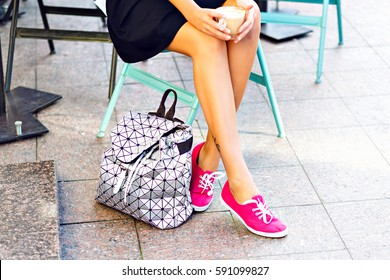 Woman's pretty legs, girl sitting in outdoor cafe, holding cup of cappuccino, coffee, late in hands. Wearing pink gumshoes, stylish silver backpack next to shoes. Outside city background.