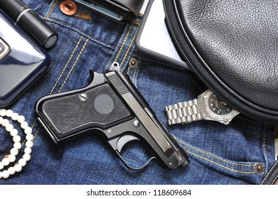 A woman's purse and  gun and accessories