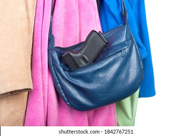 A woman's purse hanging on a coatrack with a gun in the side pocket.  Image may be used for any number of topics, including personal safety, crime, protection, and gun safety.