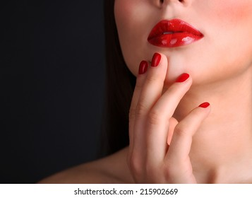 Woman's red lips and nails on dark background