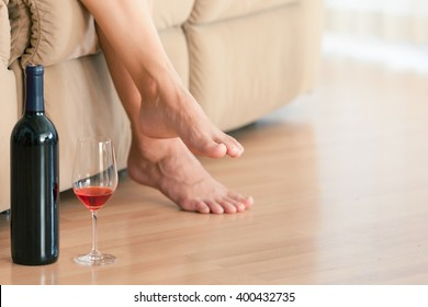 Woman's relaxing at home on the sofa with a bottle of wine and glass by her side.