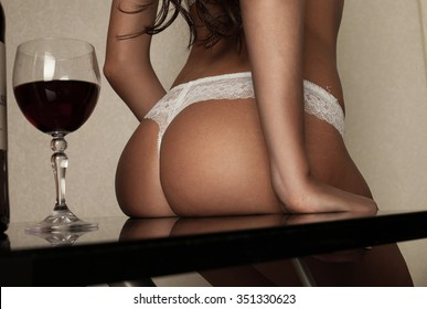 Woman's sexy buttocks in a bikini. Hot lady in white lingerie. Fashion studio shot. Slim girl. Red vine.