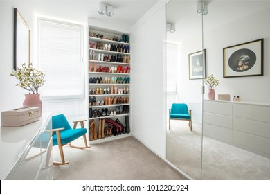 Woman's shoes on shelves in cozy dressing room interior with blue armchair and mirror