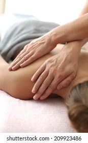 Woman's shoulder massage; hands of masseur