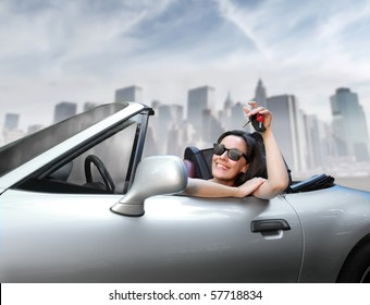 a woman's showing a key sitting on an expensive car