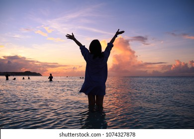 Woman's silhouette in the beautiful sunset on Tumon beach, Guam