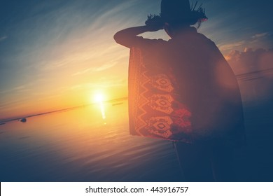Woman's silhouette in hat looking the sun rising over the horizon (lens flare effect and vintage color)