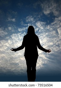 Woman`s silhouette on prayer in front of sky