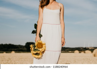 Woman's silhouette in a summer white dress with a sunflowers in hand. Beautiful rural nature on the background