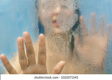 Woman`s silhouette touches glass with water drops, draws heart, stands in shower cabine alone, takes care of her beauty, has fun alone. People, freshness, hygiene, cleaning and bathing concept