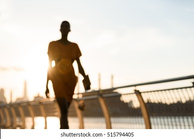 Woman's silouette walking in front of cityscape