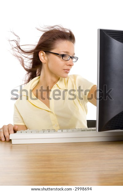 Woman's sitting at the desk. There's computer on it. Wind's blowing from LCD screen. Isolated on white in studio.