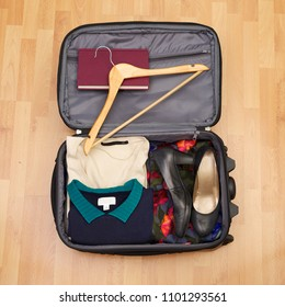 Woman's suitcase for short vacation or city trip on wooden floor