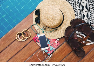 Woman's summer holidays accessories composed on wooden background near pool. Top view of essential modern young lady or girl on vacations.With copy space.