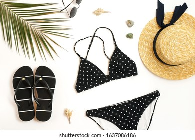 Woman's swimwear and beach accessories flat lay top view on white background. black and white polka dot bikini swimsuit, straw hat, shoes, sunglasses, palm leaf, sheels. Copy space