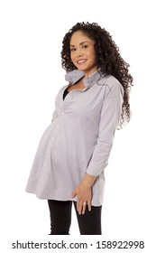 A woman's swollen belly fills out her maternity shirt, isolated on white background.