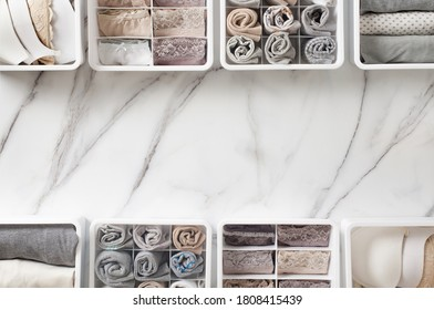 Womans underwear, pajamas and socks neatly folded and placed in closet organizer drawer divider on white marble table. Declutter wardrobe of undergarments. Keeping organized lingerie drawer storage.