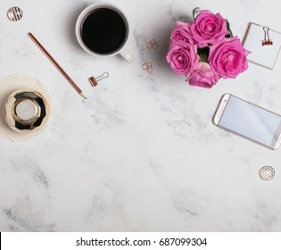 Woman's workplace with coffee, phone and roses. Top view