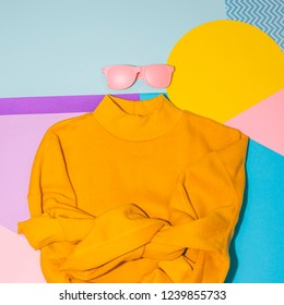Woman's yellow pullover with pink sunglasses on memphis style background. Geometry minimal concept. Fall and winter fashion.