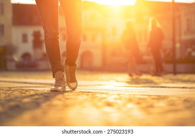 Womansfoots on the street at sunny day.