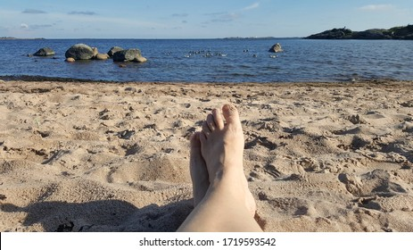 A womanwith bare feet is relaxing on the beach of Hanko on a windy spring day. Her toes are covered in the fine sand. There are birds swimming in the Baltic Sea.