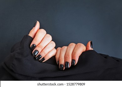 Womas hands holding black cloth demonstrating salon manicure with black nailpolish