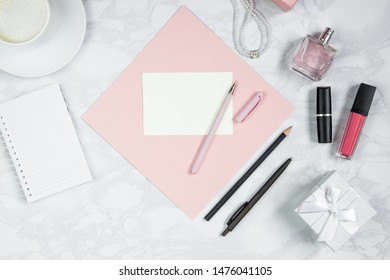 Women accessories on a white marble table. A pink sheet of paper, pen, notebook, perfume, gift box, pearls, a glass of coffee and other women's cosmetics. Layout for adding tags. Flat lay, copy space
