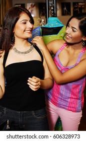 Women adjusting necklace for her friend