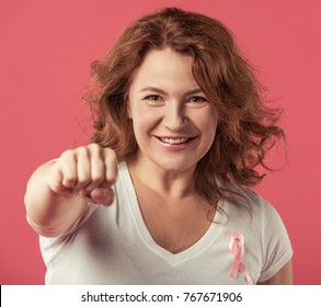 Women against breast cancer. Beautiful mature woman with pink ribbon on her chest is showing fist and smiling, on red background