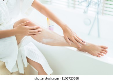 Women are applying lotion to the legs. After bath