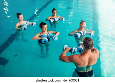 Women aqua aerobics traninig with dumbbells