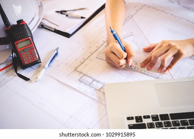 Women architect working on blueprint,engineer holding pencil pointing equipment architects on the desk with blueprint in the office.