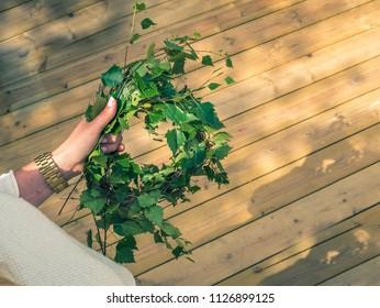 Women arranges flowers and plants for midsommar or midsummer in Sweden.