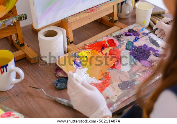 Women Artist extrudes hands in white gloves oil paint from tubes on multi-colored palette for viewing and mixing colors to start drawing pictures in art studio. On table stands glass of water, jar of