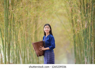 Women asia farmer in bamboo forest nature / Portrait of beautiful young asian woman happiness smile with basket for harvest agriculture in countryside village - Life young girl dress tribe