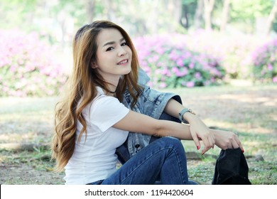 Women Asia wearing jean dresses and smiling happiness in the public park at Bangkok Thailand