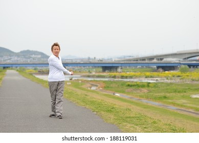 Women of Asian elderly Warming and jogging on the road to the river bank holiday
