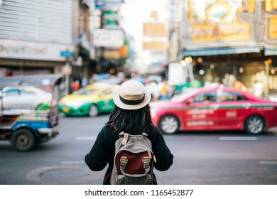 Women Asian traveling backpacker in  Yaowarat Road outdoor market in Bangkok, Thailand Travel Concept.
