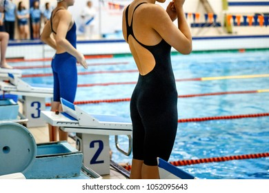 women athletes swimmers at start line in swimming pool competition
