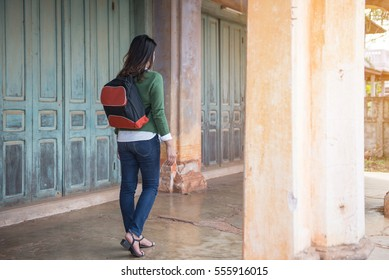 A Women with a backpack walk alone in an abandoned building.