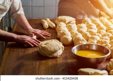 Women bake pies. Confectioners make desserts. Making buns. Dough on the table. Knead the dough.