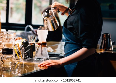 Women Barista to make a drip brewing, filtered coffee, or pour-over is a method which involves pouring water over roasted, ground coffee beans contained in a filter. in a coffee shop.vintage tone.