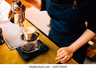 Women Barista to make a drip brewing, filtered coffee is a method which involves pouring water over roasted, ground coffee beans contained in a filter. in a coffee shop.vintage tone.