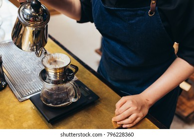 Women Barista to make a drip brewing, filtered coffee, or pour-over is a method which involves pouring water over roasted, ground coffee beans contained in a filter. in a coffee shop.