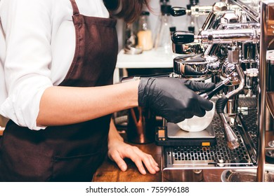 Women Barista using coffee machine for making coffee in the cafe