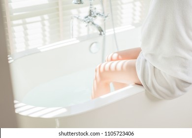 Women are bathing in the bathtub. She is about to take off the suit.